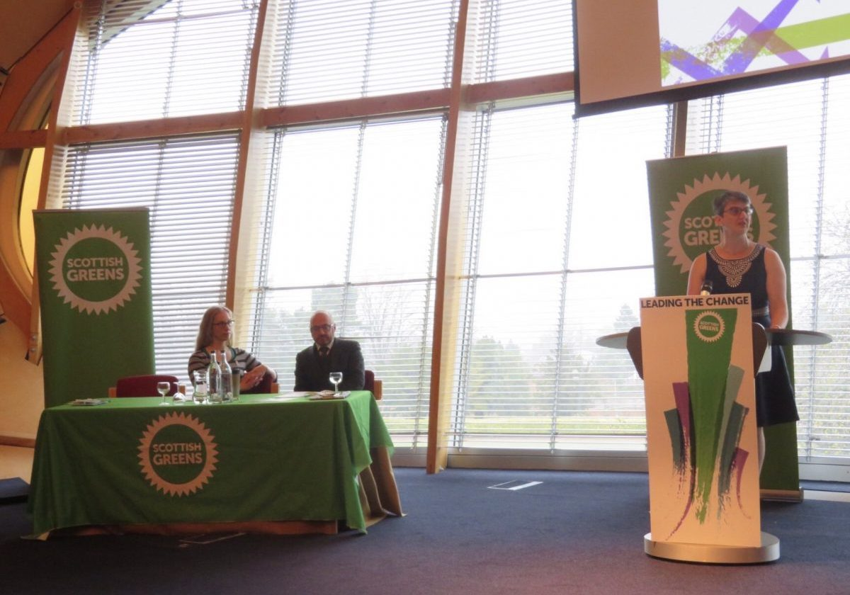 Maggie Chapman speaking at the podium to Party Conference, with Lorna Slater and Patrick Harvie sitting at the table alongside her